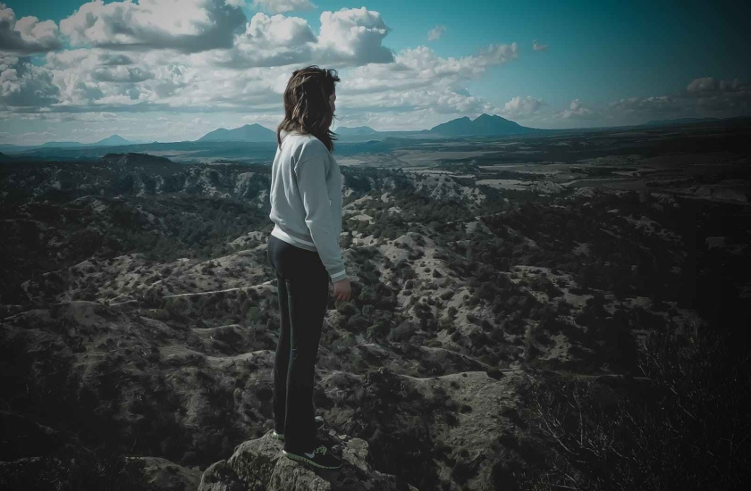 person in gray long sleeved shirt standing on top of mountain